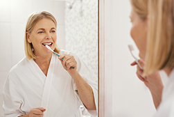 Woman practicing good oral hygiene routine to protect dental implants from Implant & Periodontal Associates NW in Richland